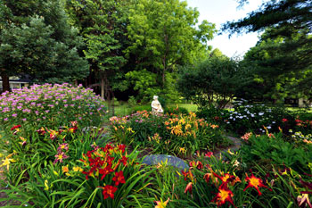 The Bange daylily garden spreads over three quarters of an acre and includes a water lily pond, a mix of evergreens, sculptures, and stonework.