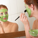 Thumb_woman-putting-on-green-face-mask-home