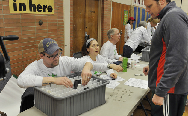 Ross Gary Alison Gary and Art Miller check in pre-registrants in the Clara Barton School gym
